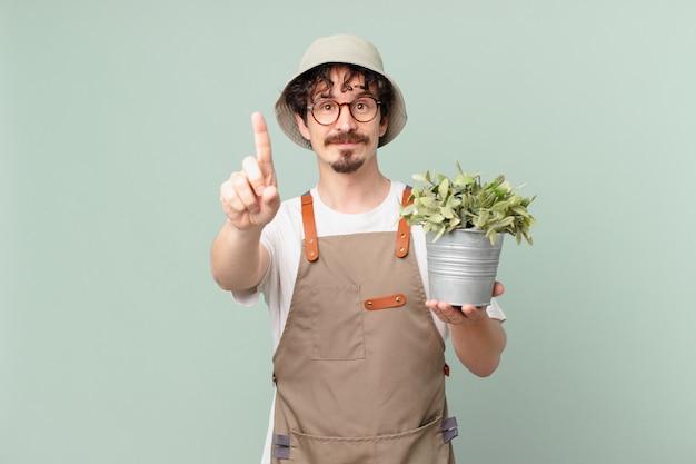 1위를 보여주며 웃고 있는 젊은 농부 남자