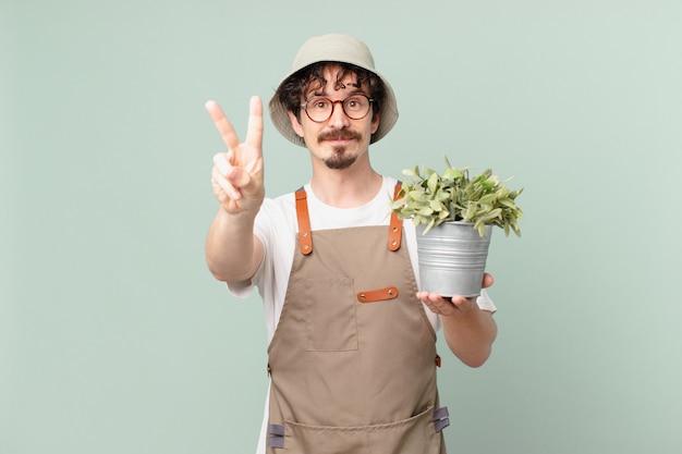 2번을 보여주며 웃고 있는 젊은 농부 남자