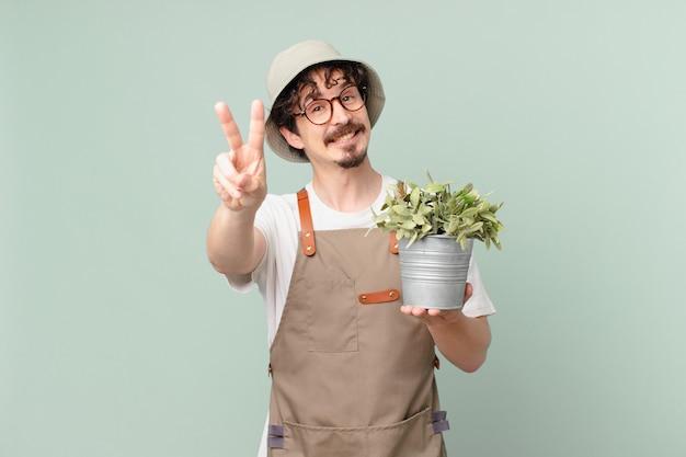 웃으면서 행복해 보이는 젊은 농부 남자, 승리 또는 평화를 몸짓