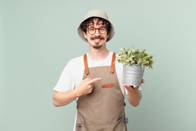 Молодой фермер весело улыбается, чувствует себя счастливым и указывает в сторону