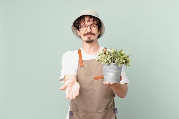 젊은 농부 남자는 친절하고 개념을 제공하고 보여주며 행복하게 웃고 있습니다.