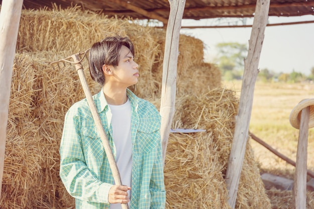 Young farmer man with pitchfork looking the sky with blurred bales of pressed straw in rural countryside storage, smart farmer concept