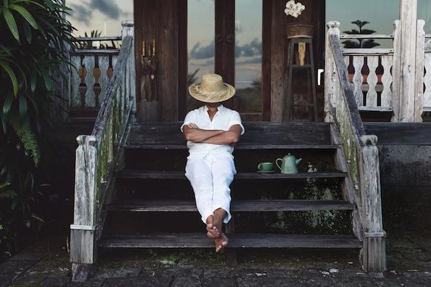 彼の家のベランダに座って寝ている若い農夫