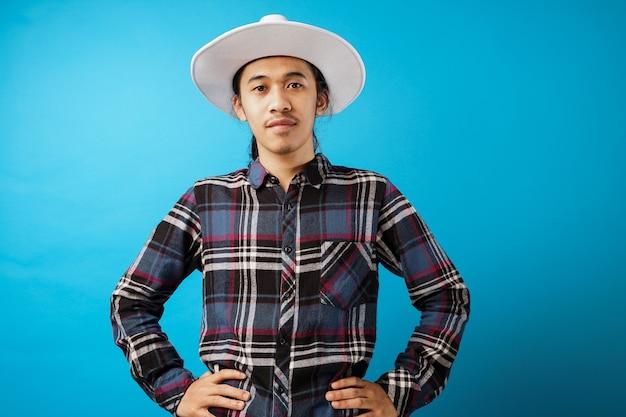 Молодой фермер в шляпе на синем фоне