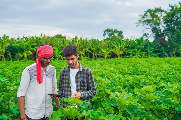 スマートフォンを使用して自分の分野でメモを取る若い農夫