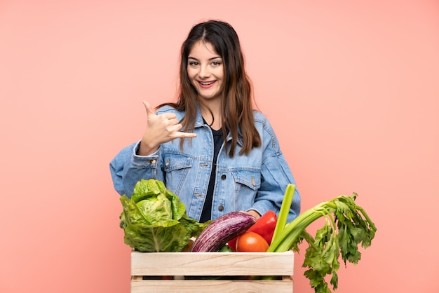 Young farmer woman holding a basket full of fresh vegetables making phone gesture