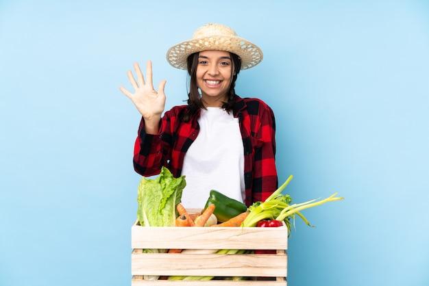 指で5を数える木製のバスケットに新鮮な野菜を保持している若い農家の女性