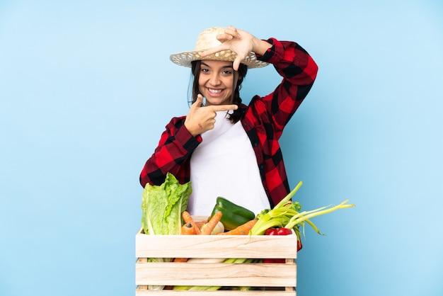 顔に焦点を当てた木製のバスケットに新鮮な野菜を保持している若い農家の女性。フレーミングシンボル