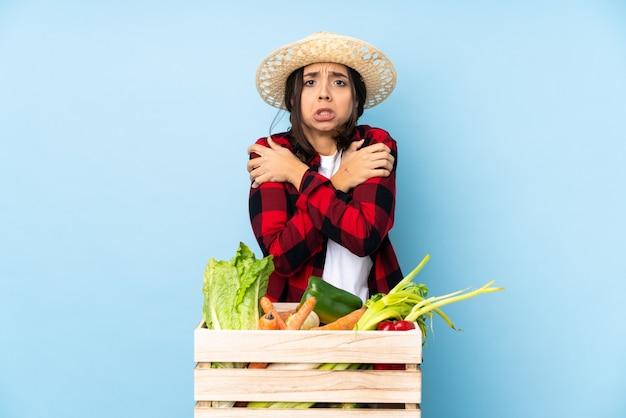 나무 바구니 동결에 신선한 야채를 들고 젊은 농부 여자