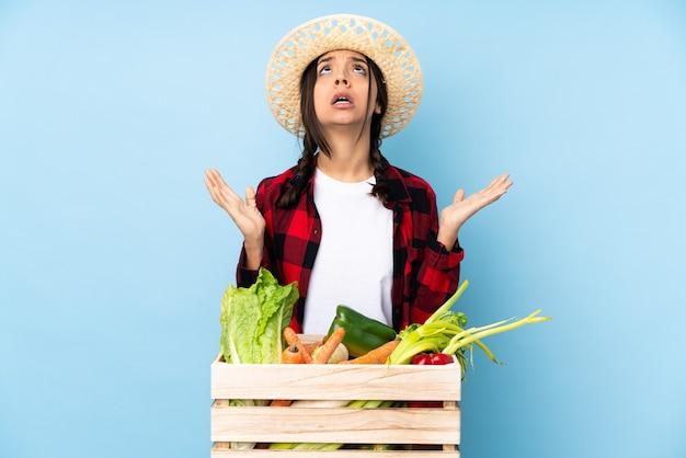 나쁜 상황에 의해 좌절 된 나무 바구니에 신선한 야채를 들고 젊은 농부 여자