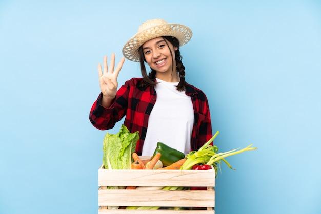 幸せな木製のバスケットに新鮮な野菜を持って、指で4を数える若い農家の女性