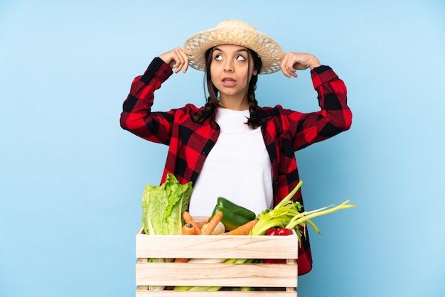 의심과 생각을 가지고 나무 바구니에 신선한 야채를 들고 젊은 농부 여자