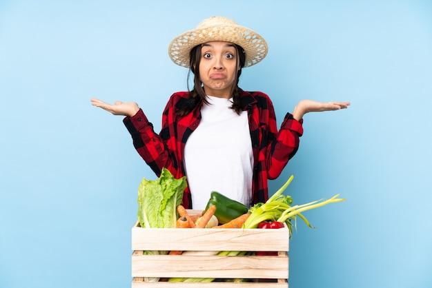 手を上げながら疑問を持っている木製のバスケットに新鮮な野菜を保持している若い農家の女性