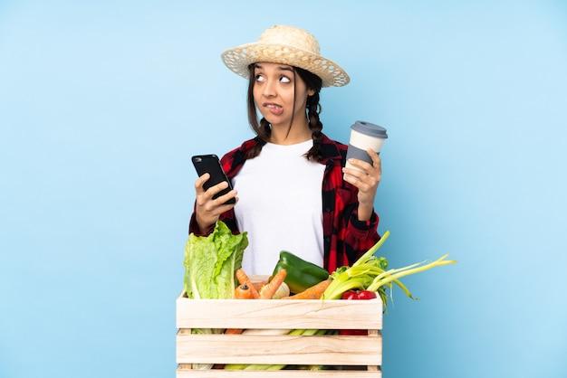 持ち帰り用のコーヒーと何かを考えながら携帯電話を保持している木製のバスケットに新鮮な野菜を保持している若い農家の女性