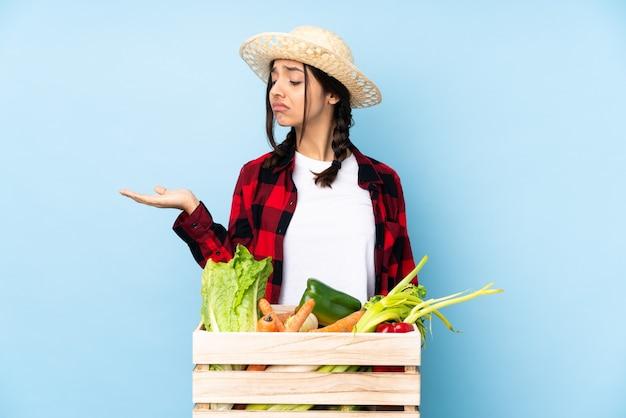 疑いを持ってコピースペースを保持している木製のバスケットに新鮮な野菜を保持している若い農家の女性