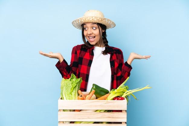 両手でコピースペースを保持している木製のバスケットに新鮮な野菜を保持している若い農家の女性