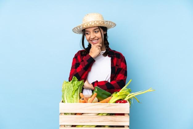 측면을 찾고 나무 바구니에 신선한 야채를 들고 젊은 농부 여자