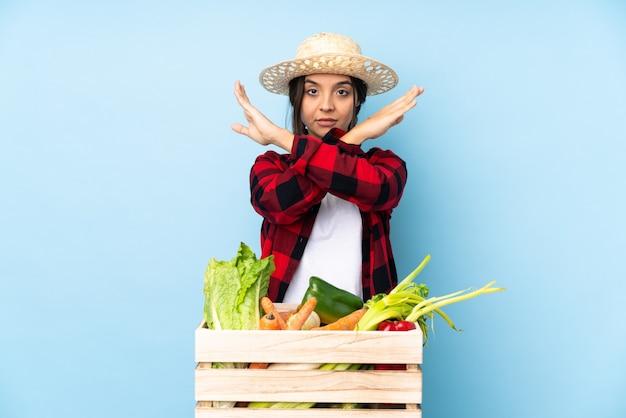 ジェスチャーをしない木製のバスケットに新鮮な野菜を保持している若い農家の女性