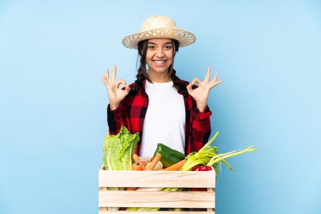 指でokサインを示す木製のバスケットに新鮮な野菜を保持している若い農家の女性
