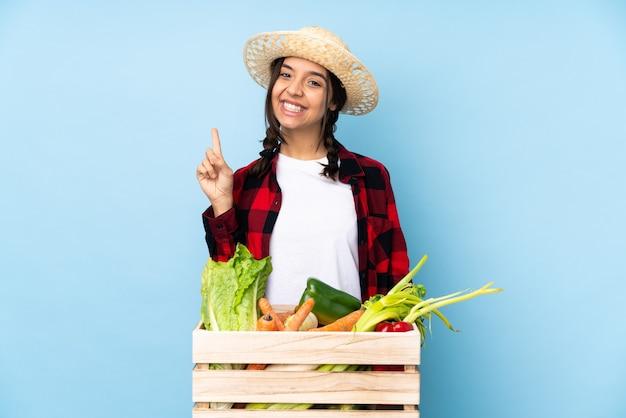 最高の兆候を示し、指を持ち上げて木製のバスケットに新鮮な野菜を保持している若い農家の女性