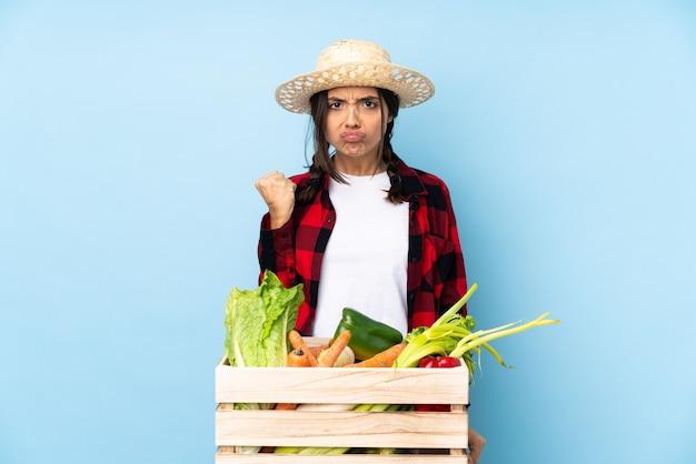 怒っているジェスチャーで木製のバスケットに新鮮な野菜を保持している若い農家の女性