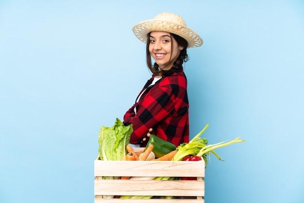 Молодой фермер женщина держит свежие овощи в деревянной корзине со скрещенными руками и смотрит вперед