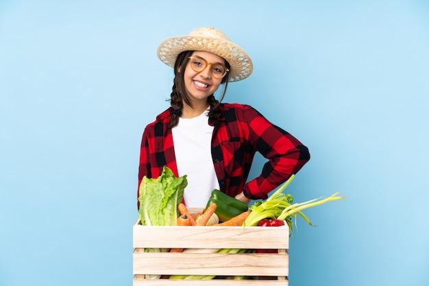 グラスと笑顔で木製のバスケットに新鮮な野菜を保持している若い農家の女性