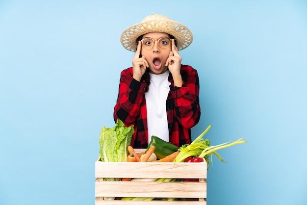 グラスと木製のバスケットに新鮮な野菜を持って驚いた若い農家の女性