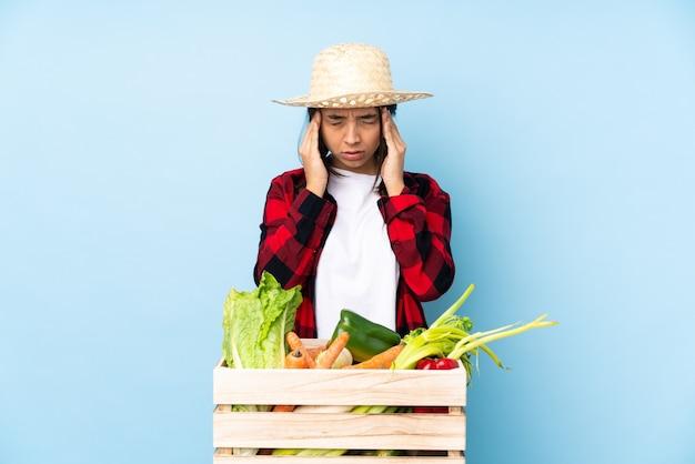 頭痛と木製のバスケットに新鮮な野菜を保持している若い農家