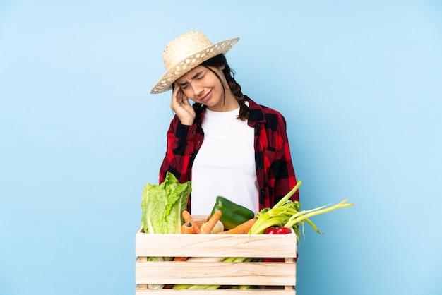 頭痛のある木製のバスケットに新鮮な野菜を保持している若い農家の女性