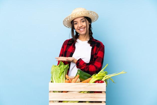 木製のバスケットに新鮮な野菜を保持している若い農家の女性