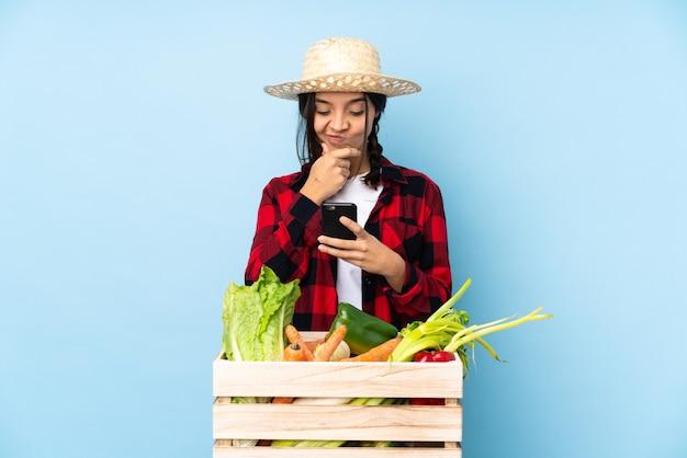 Молодой фермер женщина держит свежие овощи в деревянной корзине