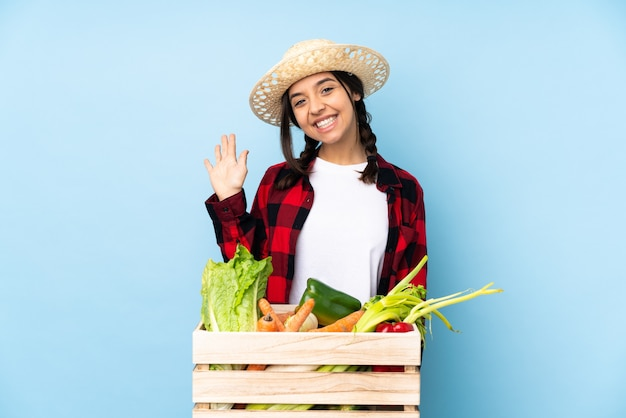 Young farmer woman holding fresh vegetables with happy expression