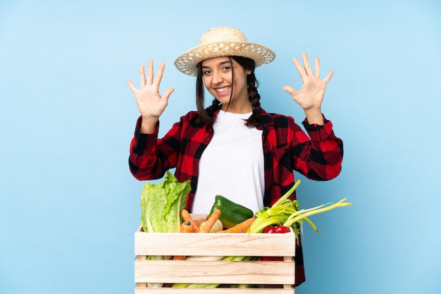 Young farmer woman holding fresh vegetables in a wooden basket counting ten with fingers