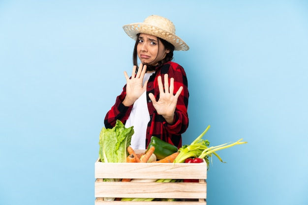 Young farmer woman holding fresh vegetables in a wooden basket nervous stretching hands to the front