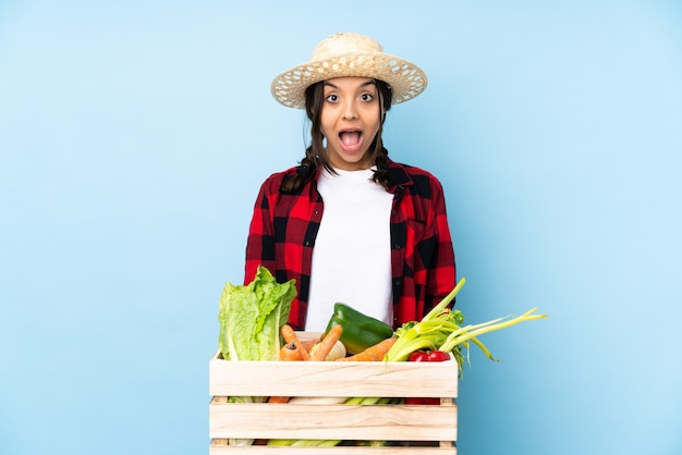 Young farmer woman holding fresh vegetables in a wooden basket with surprise facial expression