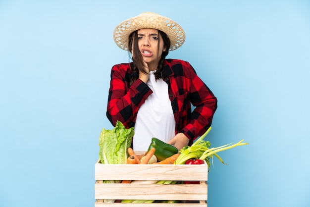 Young farmer woman holding fresh vegetables in a wooden basket with toothache