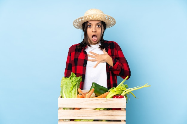 Young farmer woman holding fresh vegetables in a wooden basket