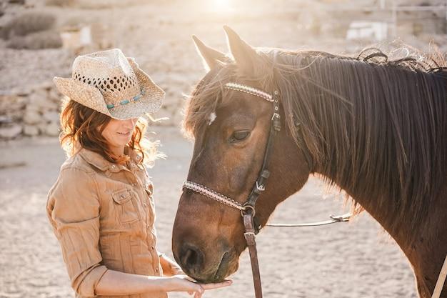 Молодая женщина-фермер играет со своей бездушной лошадью в солнечный день в загонном ранчо - понятие о любви между людьми и животными - фокус на лице девушки