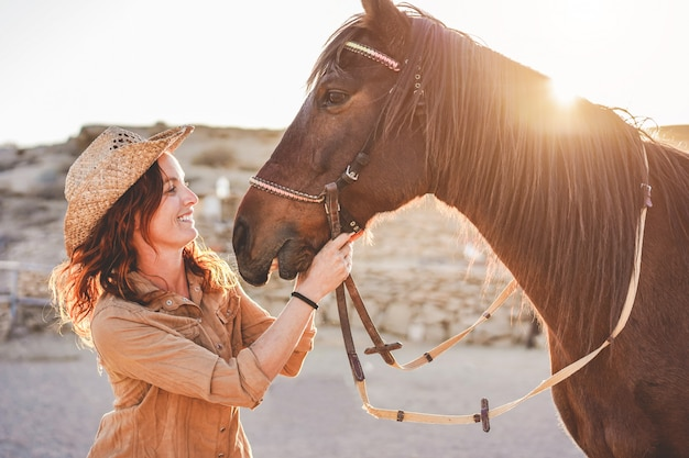 Молодая женщина фермера играя с ее бездарной лошадью в солнечном дне внутри ранчо загона