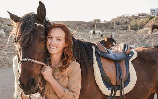 Молодая женщина-фермер играет со своей лошадью на ферме ранчо - фокус на женском лице