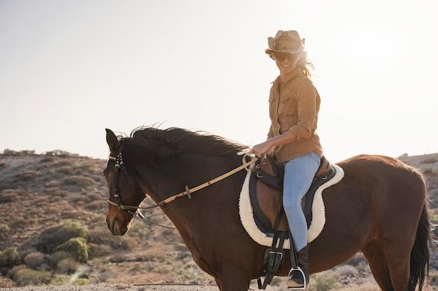 Молодая женщина-фермер верхом на лошади в солнечный день на открытом воздухе - сосредоточиться на лице