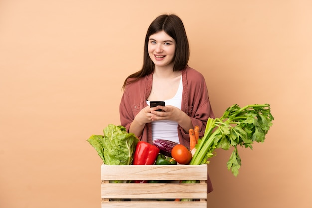Young farmer woman with freshly picked vegetables in a box sending a message with the mobile