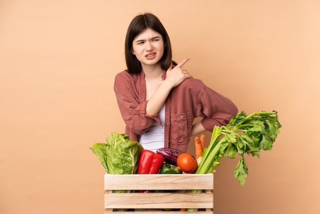 Young farmer woman with freshly picked vegetables in a box suffering from pain in shoulder for having made an effort