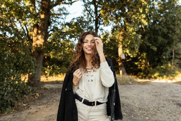 데님 재킷과 니트 스웨터를 입은 세련된 캐주얼 옷에 곱슬머리와 귀여운 미소를 지닌 젊은 패션 아름다운 행복한 여성은 시골에서 야외 산책을 하고 있습니다.