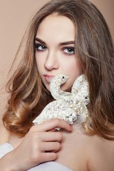 手にブローチ鳥の宝石類を持つ若いファッションブロンドの女の子