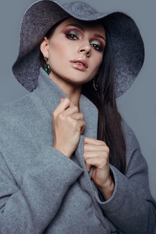Young fashion brunette woman beauty in gray coat and hat