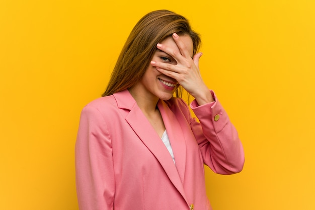 Young fashion business woman blink at through her fingers, embarrassed covering her face.