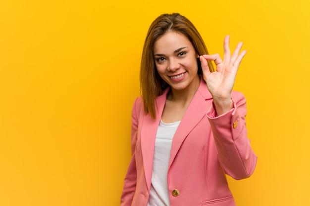 Молодая бизнес-леди моды жизнерадостная и уверенно показывая о'кеы жест.