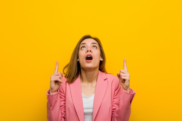Young fashion business woman pointing upside with opened mouth.